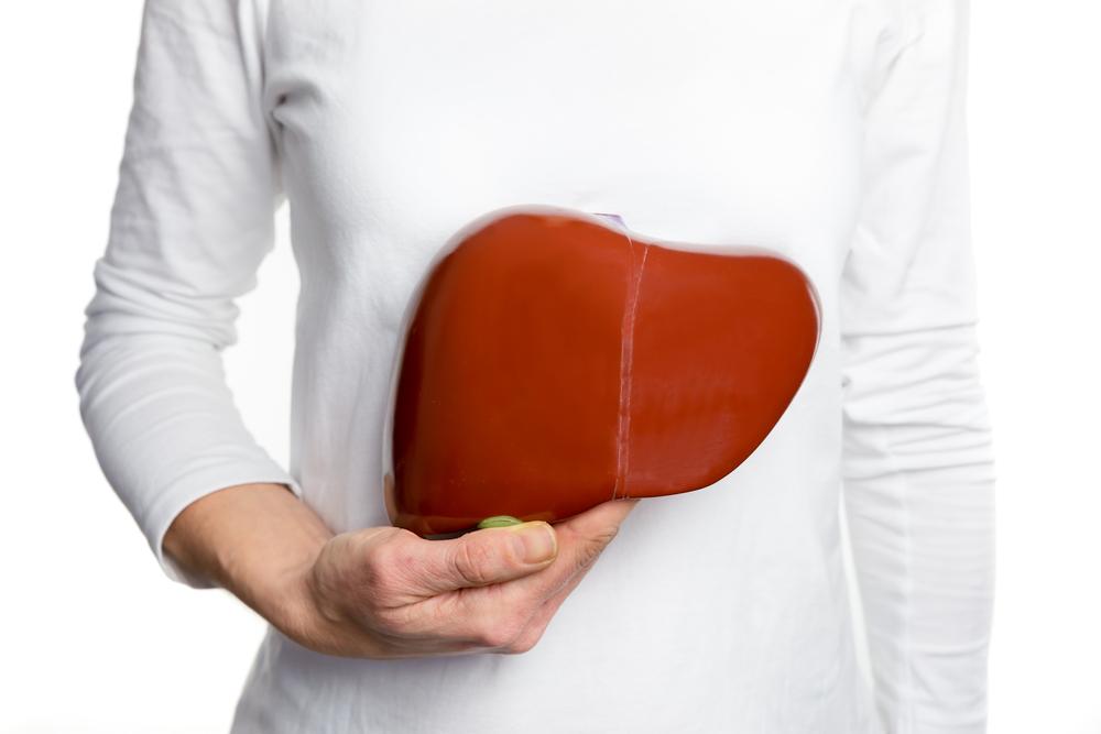 Paciente sinalizando para a ilustração de um fígado que pode ter problemas de esteatose hepática.